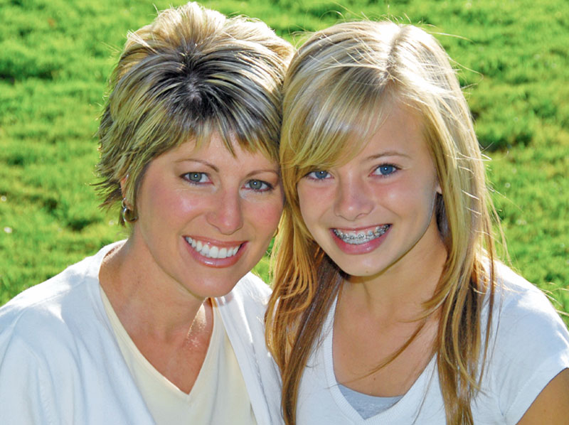 Mother and teen daughter smiling.